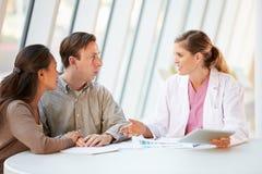 El doctor de sexo femenino Using Digital Tablet Talking con los pacientes Imagen de archivo libre de regalías
