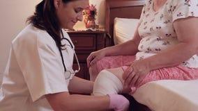 El doctor de sexo femenino venda la rodilla mayor de la mujer en casa metrajes