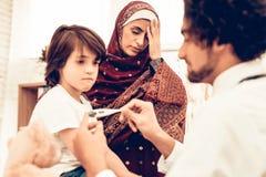 El doctor de sexo masculino árabe Examining Measuring Temperature imagenes de archivo