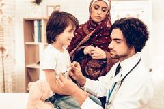 El doctor de sexo masculino árabe Examining Measuring Temperature foto de archivo libre de regalías