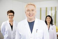 El doctor de sexo masculino confiado Standing With Colleagues imagenes de archivo