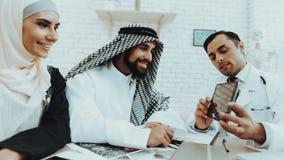 El doctor de sexo masculino Consulting Arabic Family en el hospital imagen de archivo