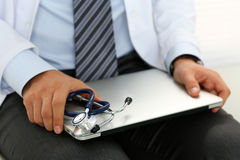 El doctor de sexo masculino de la medicina se sienta y se sostiene en el ordenador portátil de plata de las rodillas Imagenes de archivo
