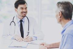 El doctor de sexo masculino elegante hermoso Talking con el paciente Imágenes de archivo libres de regalías