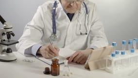 El doctor de sexo masculino escribe la prescripción en la mesa de trabajo usando la pluma y la tableta de plata almacen de metraje de vídeo