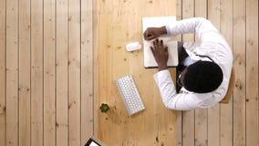 El doctor de sexo masculino escribe las notas que se sientan en el escritorio con lío en él almacen de video