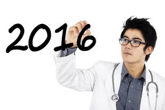 El doctor de sexo masculino escribe los números 2016 Fotos de archivo