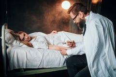 El doctor de sexo masculino hace la inyección de la jeringuilla a la mujer enferma imágenes de archivo libres de regalías