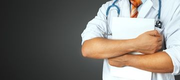 El doctor de sexo masculino irreconocible lleva a cabo documentos médicos en fondo gris Medicina, atención sanitaria, concepto de foto de archivo