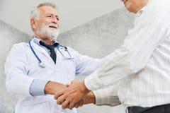 El doctor de sexo masculino mayor es apretón de manos al paciente masculino asiático Imagen de archivo