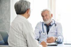 El doctor de sexo masculino mayor está hablando con el paciente masculino asiático Foto de archivo libre de regalías