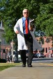 El doctor de sexo masculino mayor hermoso sonriente With Notebooks Walking imagen de archivo