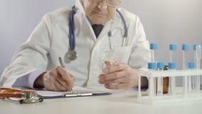 El doctor de sexo masculino que sostiene el tarro de píldoras y escribe la prescripción en la mesa de trabajo usando la pluma de  metrajes