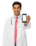El doctor de sexo masculino sonriente Showing Smart Phone Fotos de archivo libres de regalías