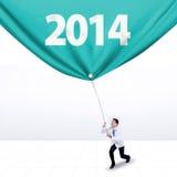 El doctor de sexo masculino tira de una bandera del Año Nuevo 2014 Foto de archivo libre de regalías
