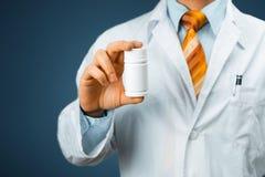 El doctor de sexo masculino In White Coat con un estetoscopio en el hombro que sostiene una botella de píldoras entre sus fingere Foto de archivo