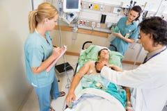 El doctor Defibrillating Critical Patient en hospital Foto de archivo
