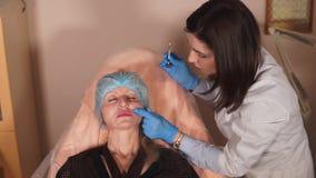 El doctor del cosmetólogo comprueba cómo los llenadores tienen resuelto almacen de video