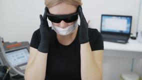El doctor del cosmetologist de la cámara lenta pone en los vidrios protectores especiales antes de procedimiento almacen de metraje de vídeo