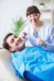 El doctor del dentista de la mujer con el paciente masculino en hospital Imagen de archivo