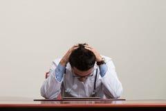 El doctor desesperado Holding Hands On su cabeza Fotografía de archivo libre de regalías