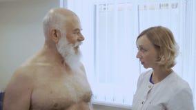El doctor dice la conclusión al hombre mayor después de chekicing sus pulmones con el estetoscopio almacen de video
