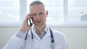 El doctor Discussing con el paciente durante charla del teléfono almacen de metraje de vídeo