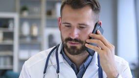 El doctor Discussing con el paciente durante charla del teléfono metrajes