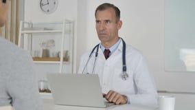 El doctor Discussing con el paciente en la clínica, tratamiento de la salud metrajes