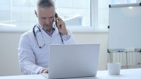 El doctor Discussing con salud paciente en llamada de teléfono almacen de metraje de vídeo