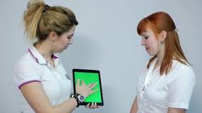 El doctor Discussing Eesults con el paciente en la tableta, pantalla verde almacen de video