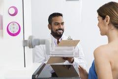 El doctor Discussing With Patient antes de la prueba de la radiografía del mamograma Foto de archivo libre de regalías