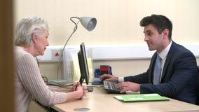 El doctor Discussing Test Results con el paciente femenino mayor metrajes