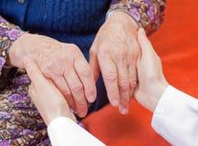El doctor dulce joven lleva a cabo la mano de la mujer mayor Fotos de archivo