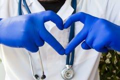 El doctor en capa del laboratorio médico con el estetoscopio muestra la forma del primer del corazón de la tarjeta en frente, hec fotografía de archivo libre de regalías