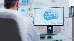 El doctor en centro de investigación moderno mira la exploración de cerebro 3D almacen de metraje de vídeo