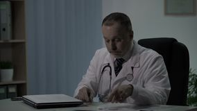 El doctor en deber de noche llena tarjetas de los pacientes y decide tomar siesta en silla acogedora metrajes