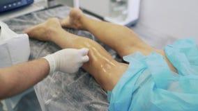 El doctor en guantes estéril moja algodón en líquido desinfectante, desinfecta la pierna paciente antes de cirugía de la variz almacen de metraje de vídeo