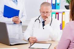 El doctor en la tabla examina los resultados de su paciente analiza, doc. en oficina médica fotografía de archivo