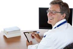 El doctor en su escritorio escribe el informe médico Imagen de archivo libre de regalías