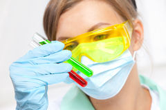 El doctor en una máscara examina los tubos de ensayo Fotografía de archivo