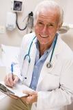 El doctor envejecido medio Writing On His Clipboard imagen de archivo libre de regalías