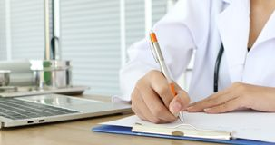 El doctor escribe la nota en el papel del tablero en hospital metrajes