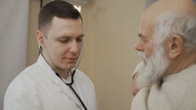 El doctor escucha corazón del hombre mayor con el estetoscopio almacen de video