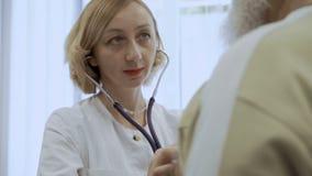 El doctor escucha corazón del viejo hombre con el estetoscopio almacen de metraje de vídeo