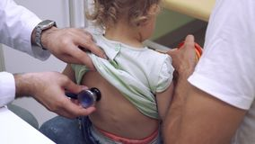 El doctor escucha detrás de niña con el estetoscopio almacen de metraje de vídeo