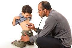 El doctor está comprobando a un muchacho con un estetoscopio foto de archivo libre de regalías