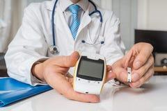 El doctor está dando glucometer al paciente diabético al azúcar de sangre de la medida Concepto de la diabetes fotos de archivo