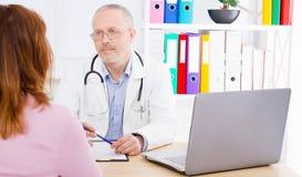El doctor está discutiendo algo con el paciente de la mujer y se está sentando en oficina médica foto de archivo