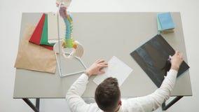 El doctor está haciendo su papeleo, haciendo un horario del deber que se sienta en el escritorio almacen de video